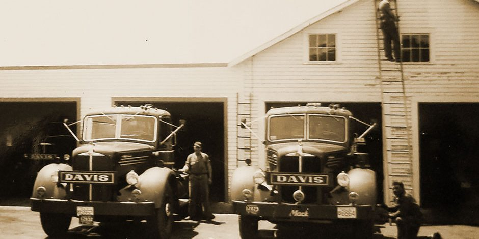 A black and white aged photo of the Davis Oil building and trucks
