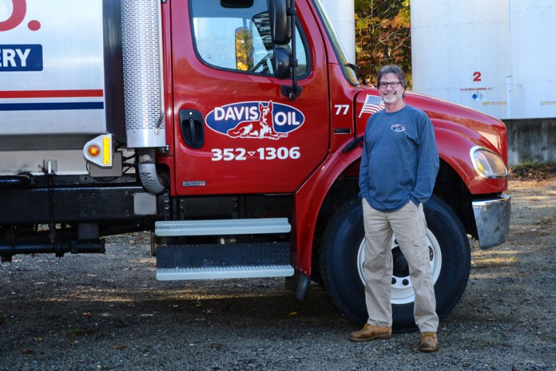 Davis Oil employee standing in front of one of their full trucks.